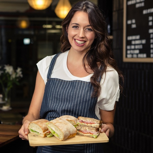Employee holding a tray of sandwiches