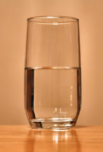 A close up of a glass of water filled half way