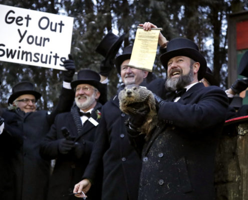 Groundhog Club co-handler Al Dereume, second from right, holds Punxsutawney Phil, the weather prognosticating groundhog, during the 133rd celebration of Groundhog Day on Gobbler's Knob in Punxsutawney, Pa. Saturday, Feb. 2, 2019. Phil's handlers said that the groundhog has forecast an early spring. (AP Photo/Gene J. Puskar)